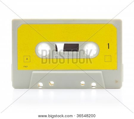 Early 70's cassette tape isolated on white with slight reflection.  Yellow label.