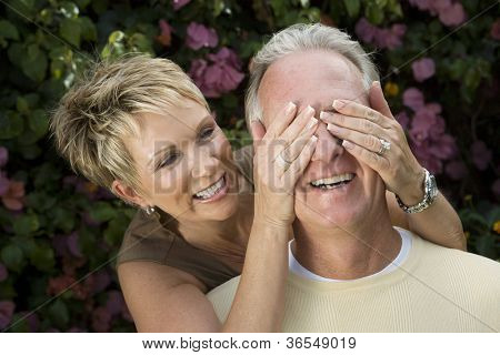 Playful middle aged woman covering eyes of husband