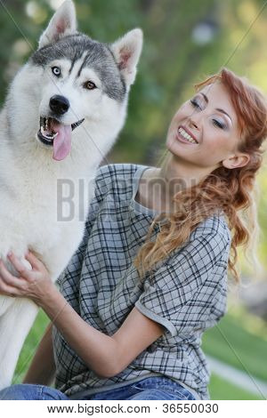 young happy woman with haski dog outdoors