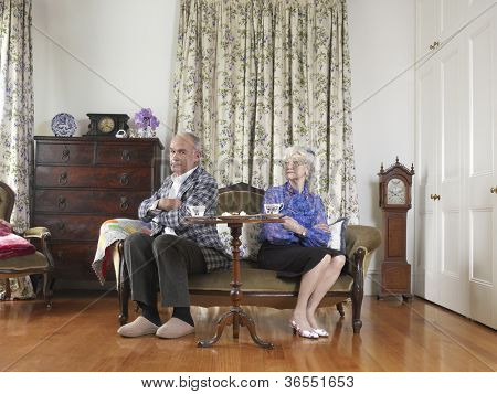An angry senior couple sitting on sofa at home