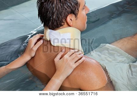 Young man wearing neck brace being massaged by female while sitting in pool