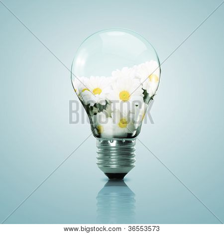 Electric light bulb and flower inside it as symbol of green energy