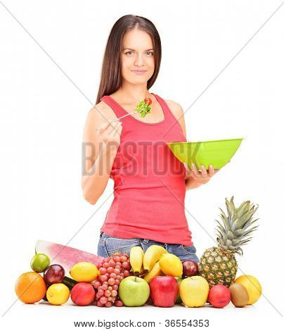 Young woman eating a salad standing behind a pile of fruits isolated on white