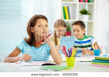 Portrait of lovely girl concentrating on drawing at workplace with schoolmates on background