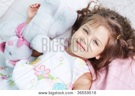 Portrait of lovely girl lying with teddybear and looking at camera