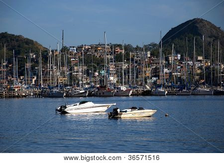 Slum near the sea with rich boats and yachts in front