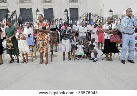 Haitians praying outside a collapsed church.