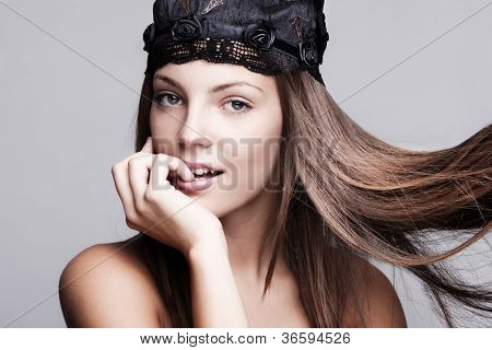 young brunette woman with smooth silky hair in motion wearing satin cap studio shot