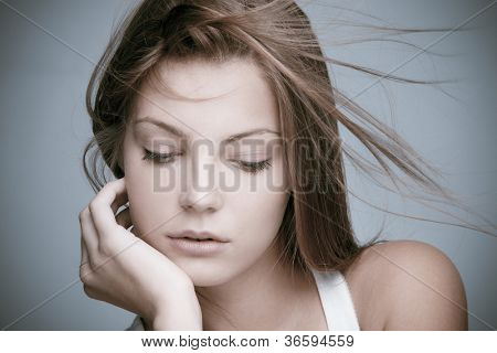 natural beautiful young  woman hand on chin  looking down hair in motion  close-up shot studio