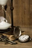 Vintage grunge still life with hour glass, pocket watch, old brass keys and tattered book.