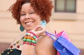 image of plus size model  - Plus size model smiling about a purchase and looking into a shopping bag - JPG