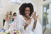 Portrait of an excited bride showing her engagement ring with friends celebrating  party in the back
