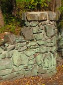 stock photo of fieldstone-wall  - stone wall and column made with irregular stone with green coloring - JPG