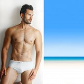 stock photo of buff  - Sexy portrait of a very muscular shirtless male model in underwear against white wall in sensual pose with tropical paradise in background - JPG