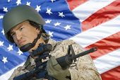 picture of assault-rifle  - Soldier with assault rifle in front of US flag - JPG