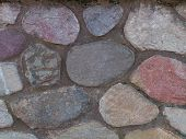 image of fieldstone-wall  - stone wall with rounded multi colored stones - JPG