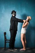 man with black mask strangle  young girl studio shot