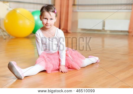 Cute Little Balerina Stretching On Floor