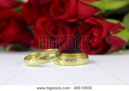 wedding rings and roses on the white background