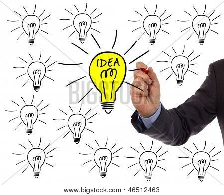 Businessman drawing a light bulb on a whiteboard concept for bright idea and inspiration