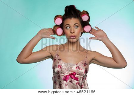 Portrait of a vain pretty young woman wearing a flowery satin summer pajama showing her hair rollers