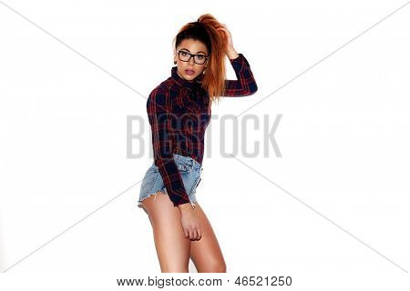 Fashion portrait of a pretty teenage girl on white background, wearing glasses, a checkered red shirt, skimpy jeans shorts and a pony-tail