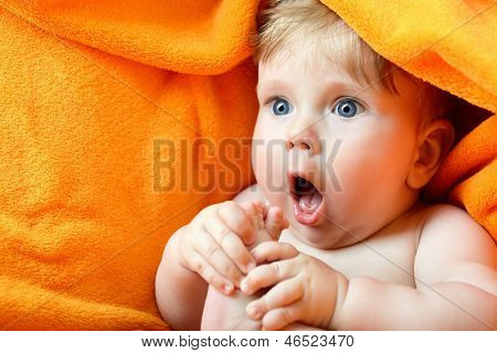 portrait of cute baby boy lying on orange plaid and sucking his leg's finger