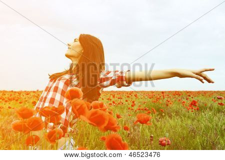 Young beautiful woman walking and dancing through a poppy field, summer outdoor. Toned, noise added.