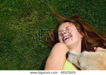 beautiful young happy laugh girl playing with her dog outdoor