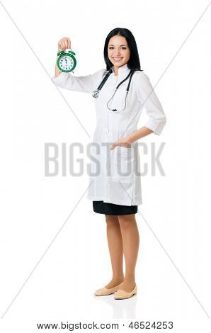 Female doctor holding a green alarm clock, isolated on white background