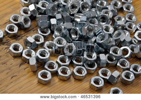 A pile of metal nuts on a table
