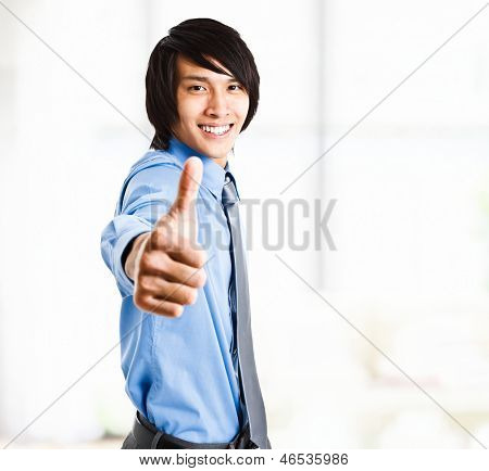 Portrait of an handsome oriental businessman giving thumbs up