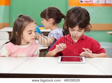 Little boy using digital tablet with female friend at desk in kindergarten