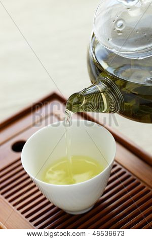 chinese tea serving, pouring from glass teapot in tasting cup