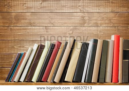Old books on a wooden shelf. No labels, blank spine.