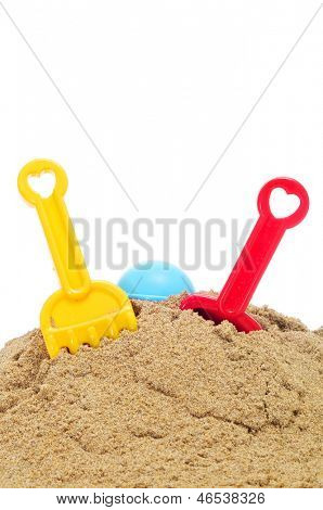 toy shovels and rakes on the sand, on a white background
