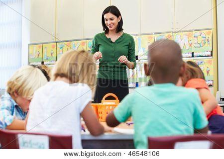 Lehrer im Gespräch mit elementaren Schüler im Klassenzimmer