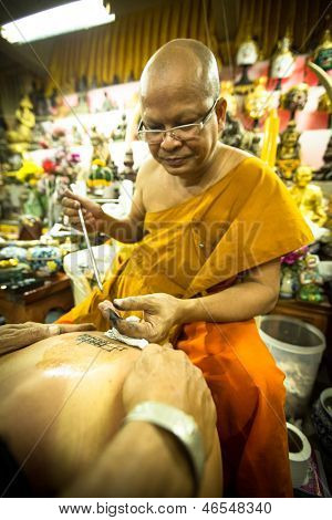 NAKHON CHAI, THAILAND - MAR 1: Unidentified monk makes traditional Yantra tattooing on Mar 1, 2012 in Nakhon Chai, Thailand. Yantra tattoo also called Sak Yant, practiced in Southeast Asian countries.