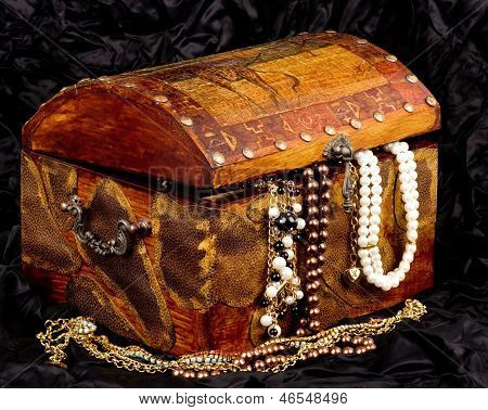 Vintage wooden treasure trunk with jewelry on black background