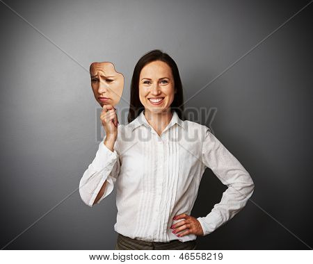 young woman hiding her good mood under sad mask