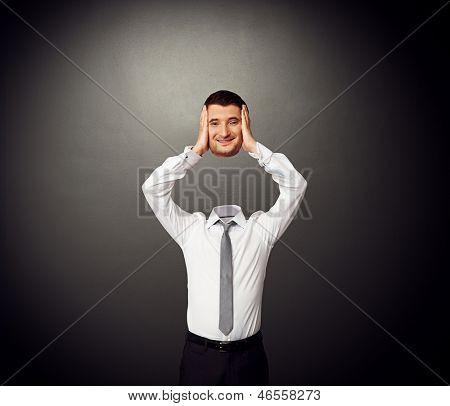 businessman holding his smiley head in hands. photo over dark background