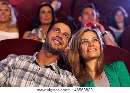 Happy young couple watching movie in cinema, smiling.