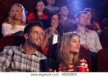 Young people sitting at auditorium of movie theater, watching movie.