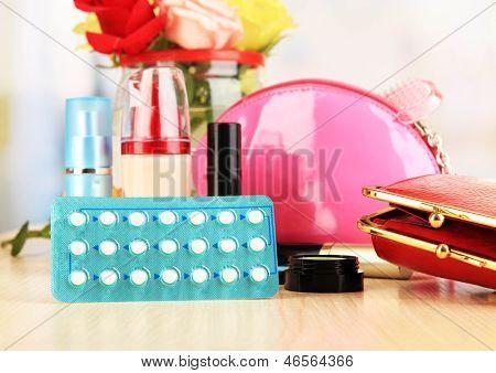 Pílulas hormonais na mesa de cabeceira da mulher no fundo da sala