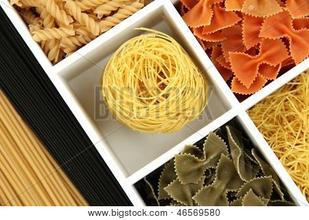 Different types of pasta in white wooden box sections close-up