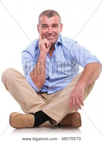 casual senior man sitting on the floor with his legs crossed and holding his hand at his chin, in a pensive way, while smiling for the camera. isolated on white background