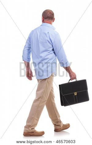 full length picture of a casual senior man walking away from the camera with a suitcase in his hand. isolated on white background