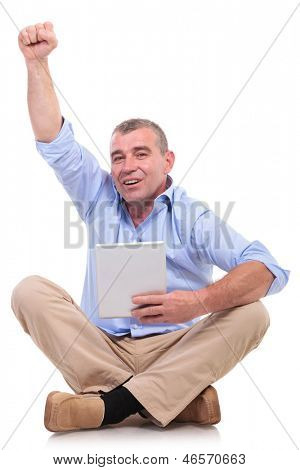 casual senior man sitting on the floor with his legs crossed and holding a tablet in his hand while cheering. isolated on white background
