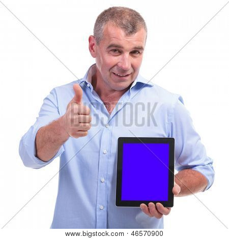 casual senior man presenting a tablet with an empty blue screen and showing the thumbs up gesture while looking at the camera. isolated on white background