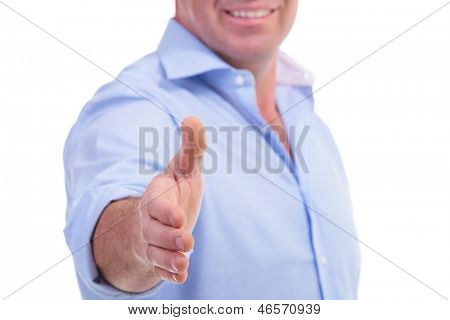 cutout picture of a casual senior man offering a handshake with a smile, with focus on the hand. isolated on white background